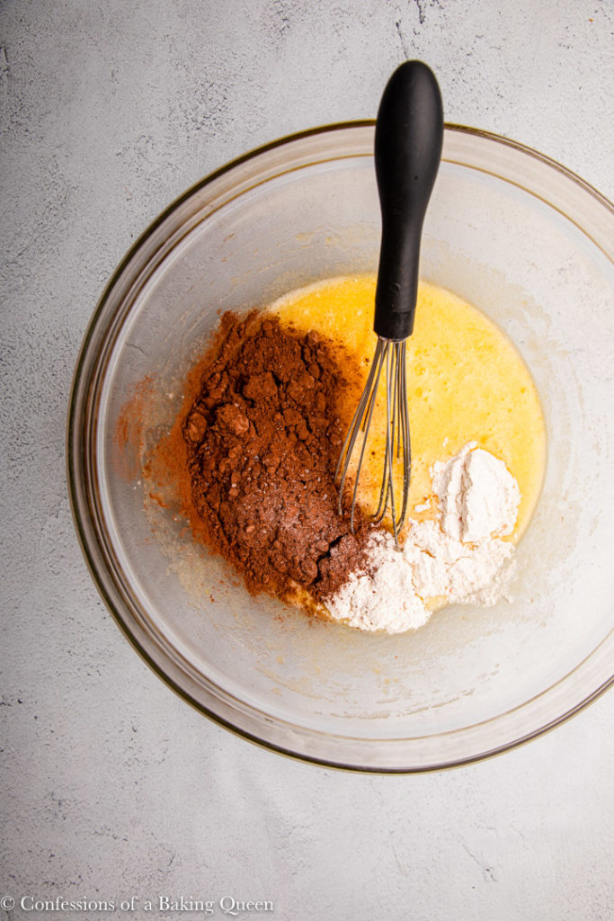 cocoa powder and flour added to egg and sugar mixture in a large glass bowl