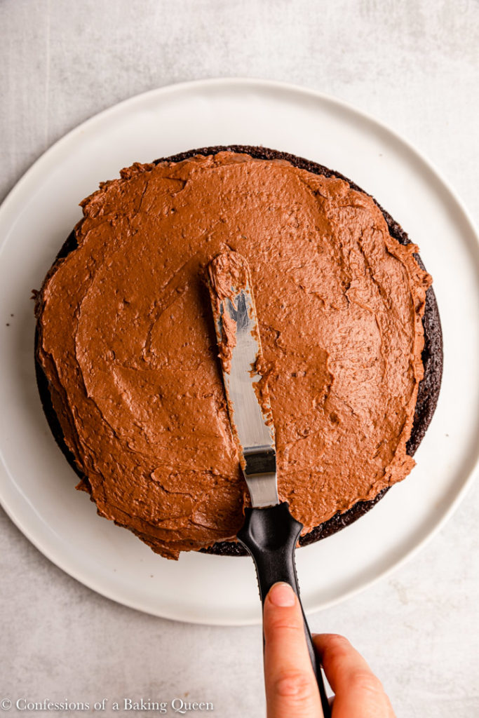 hand holding an angled spatula to spread chocolate frosting on top of a chocolate cake layer on a light grey surface
