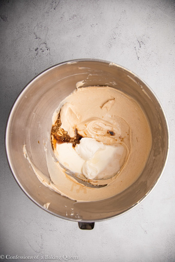 sour cream, heavy cream, and vanilla added to cream cheese mixture in a metal mixing bowl