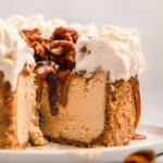 cut open pecan pie cheesecake on a white plate