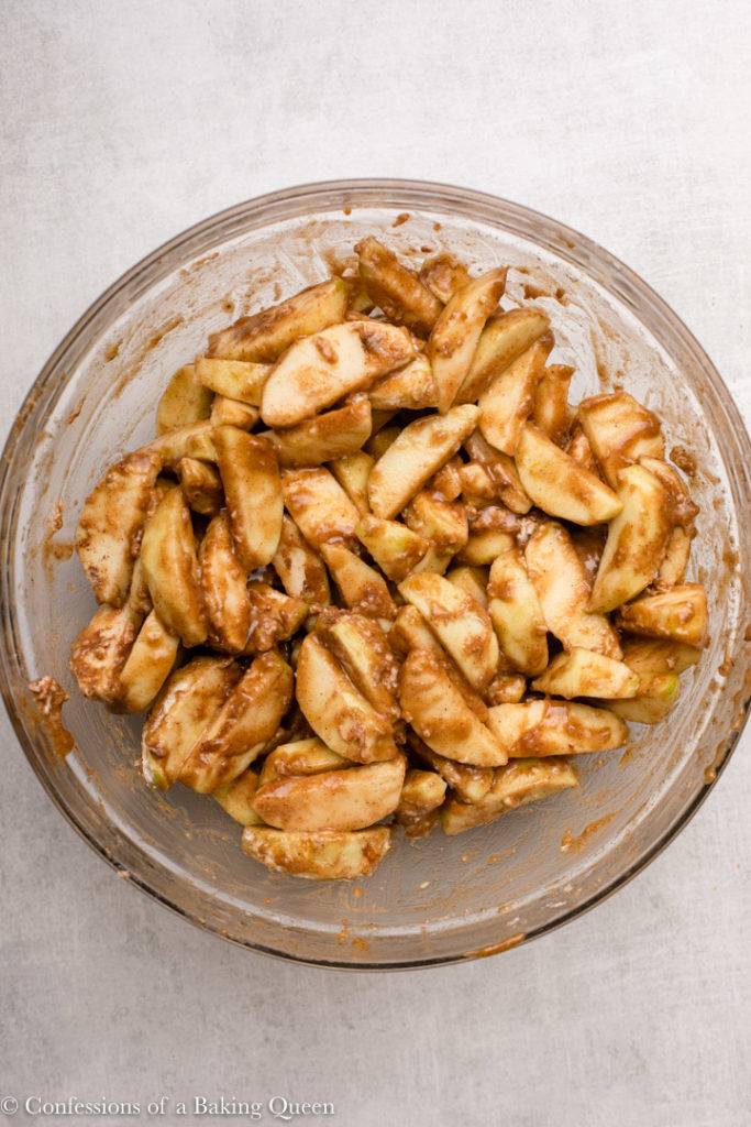 apple slices mixed with spices, flour and sugar in a glass bowl