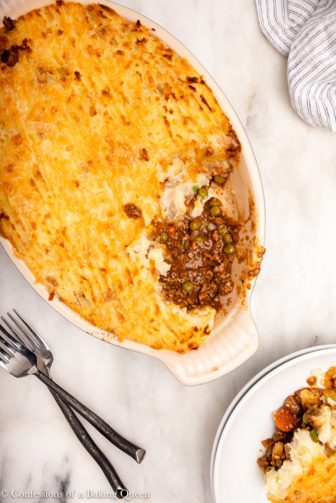 baked shepherds pie next to plates with a slice of shepherds pie