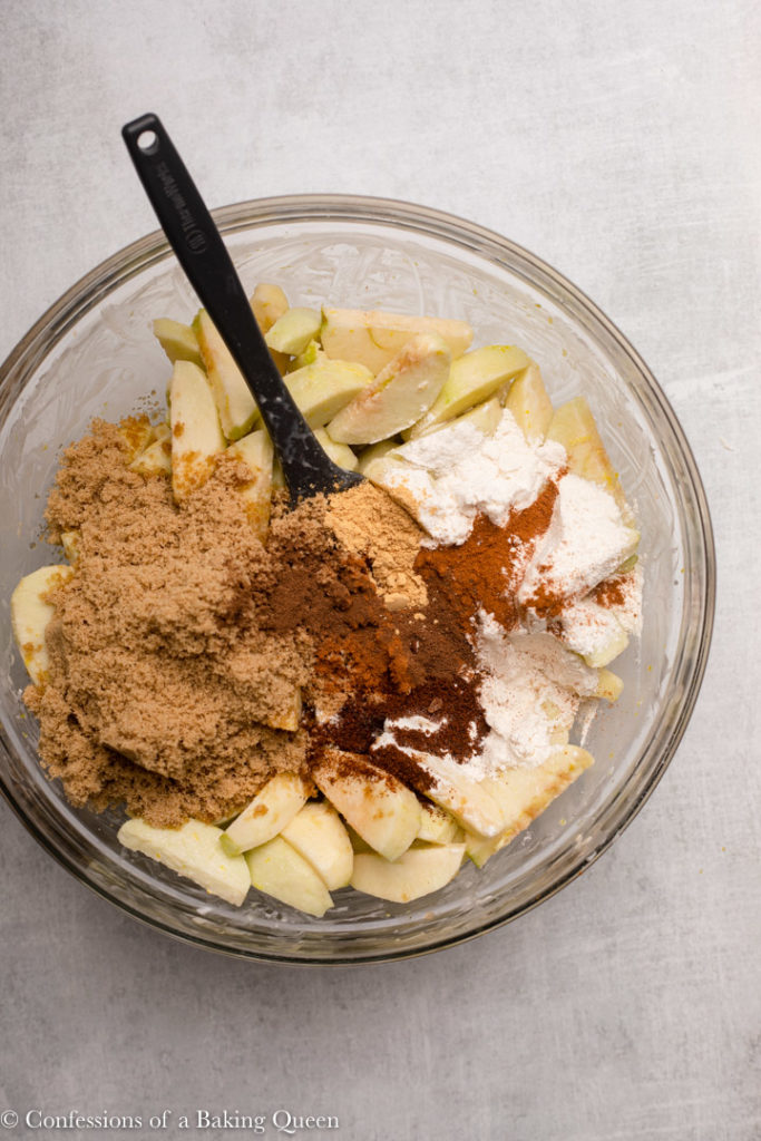 brown sugar, flourl and spicces added to sliced apples in a glass bowl