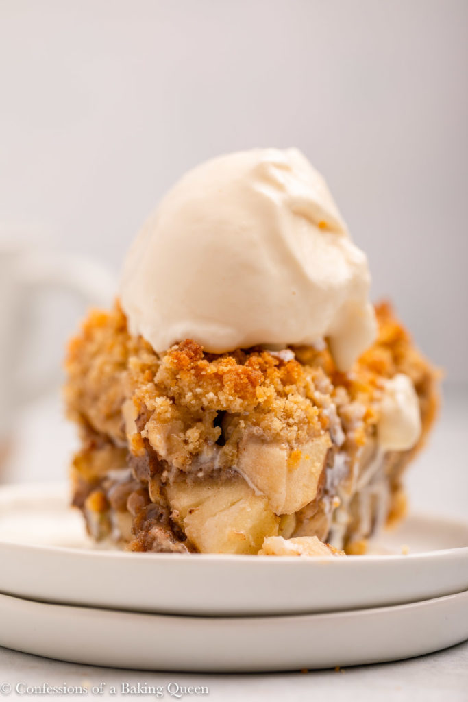 close up of a slice of dutch apple pie with ice cream on a white plate