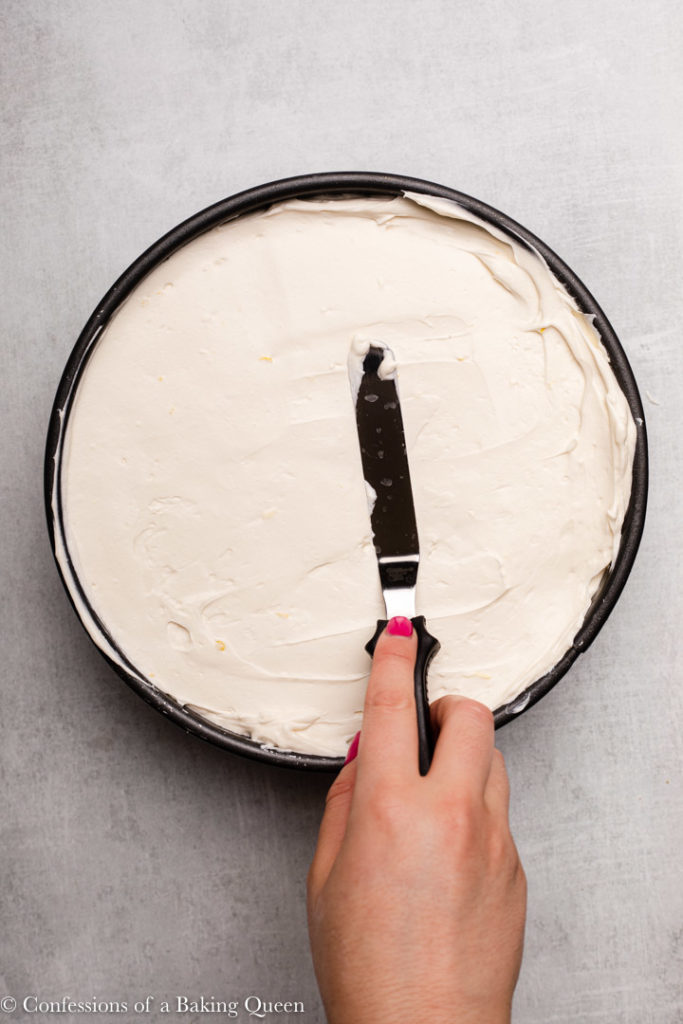 hand spreading no bake cheesecake into a springform pan