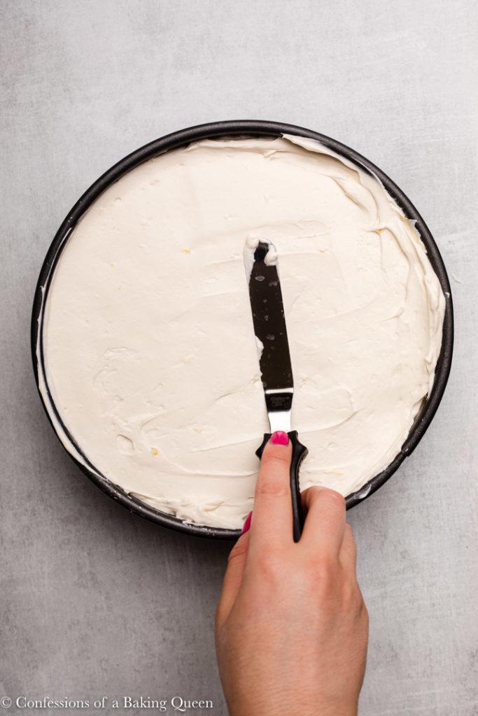 hand spreading no bake cheesecake into a springform pan