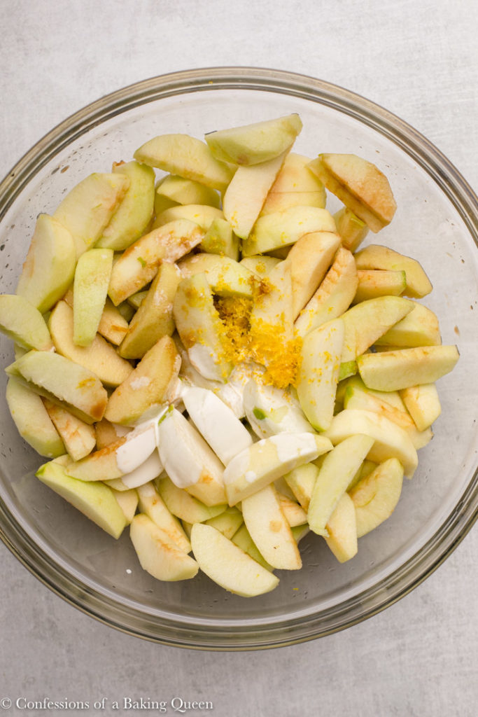 peeled apple slices in a glass bowl with lemon zest and heavy cream
