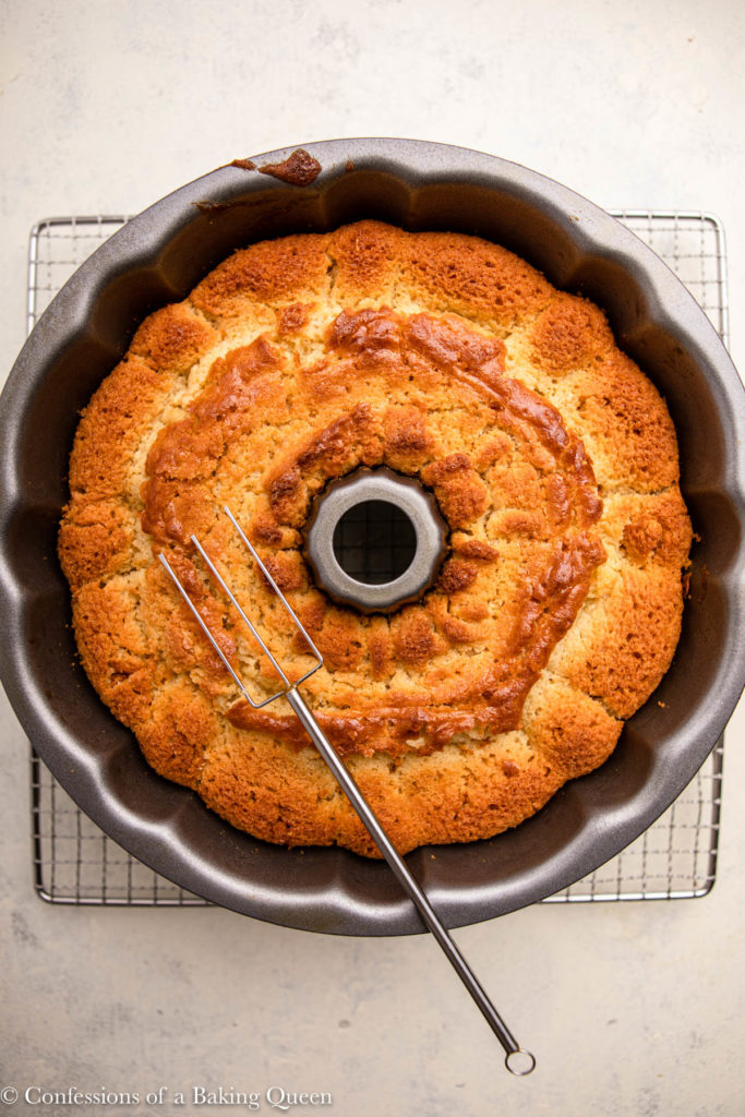 kentucky butter cake batter baked and cooling on a wire rack with a metal skewer on top