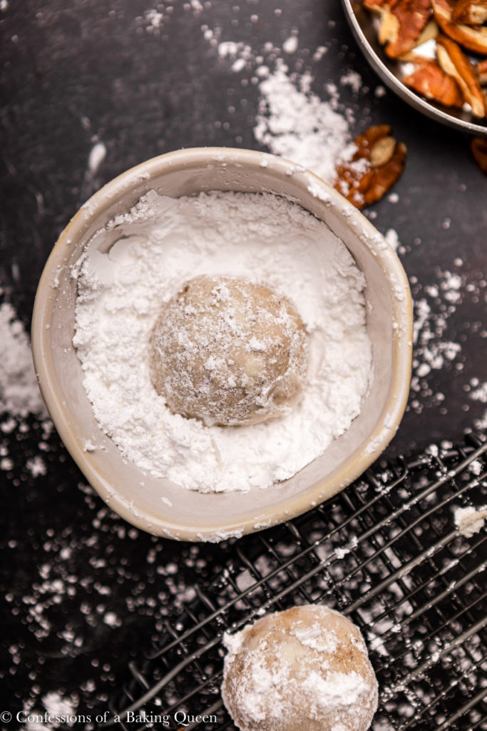 mexican wedding cookie in a small bowl of powdered sugar