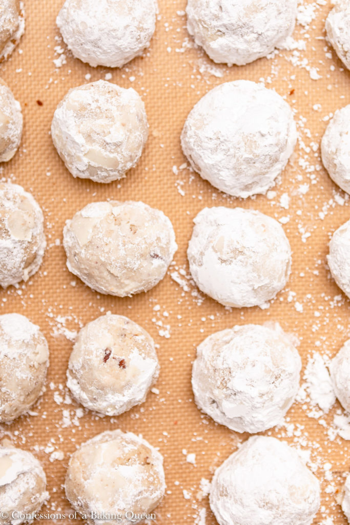 mexican wedding cookies baked and dipped in powdered sugar on a silpat liner