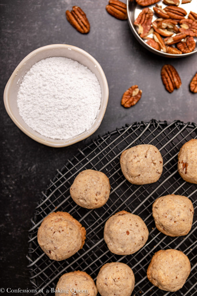 mexican wedding cookies on a wire rack next to a bowl of powdered sugar and cup of pecans
