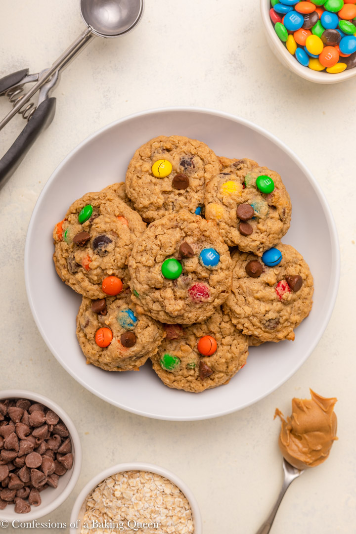 plate full of monster cookies next to a cup of chocolate chip, oats, and m&ms and a spoon full of peanut butter