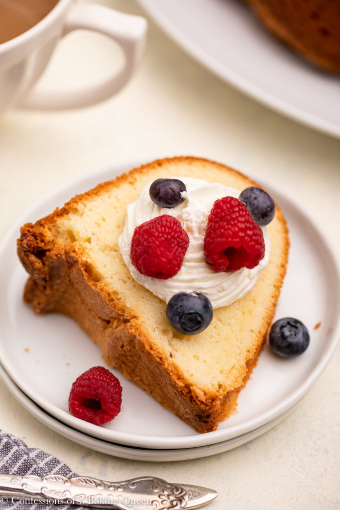slice of cream cheese pound cake with whipped cream and fresh berries on a white plate
