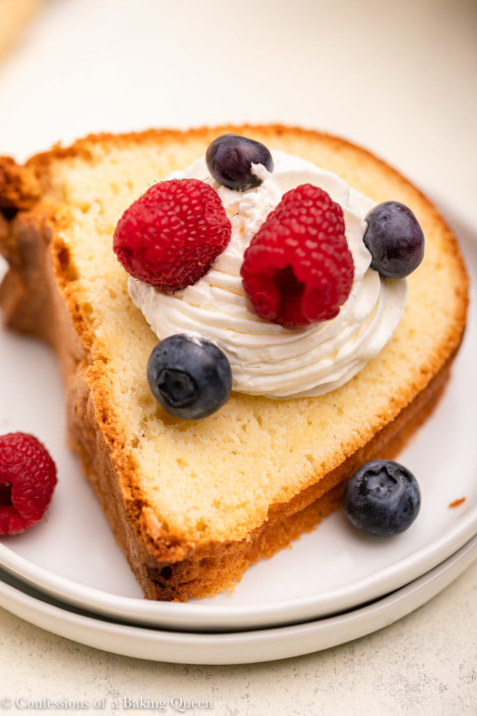 up close of a slice of cream cheese pound cake with whipped cream and berries