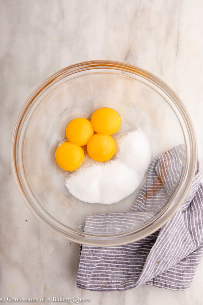 4 egg yolks and sugar in a glass bowl