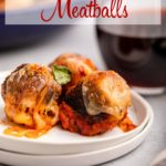 three chicken parm meatballs on a white plate