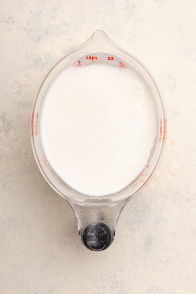 buttermilk in a liquid measuring cup on a white surface