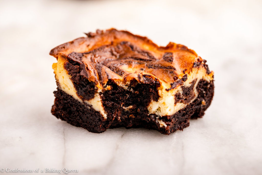 cheesecake brownie with a bite taken out on a white marble surface