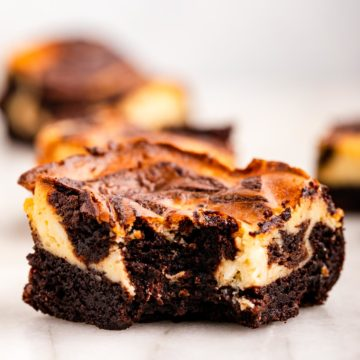 cheesecake brownie with a bite taken out on a white marble surface (