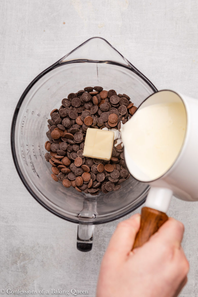 cream poured into a glass bowl of chocolate and butter
