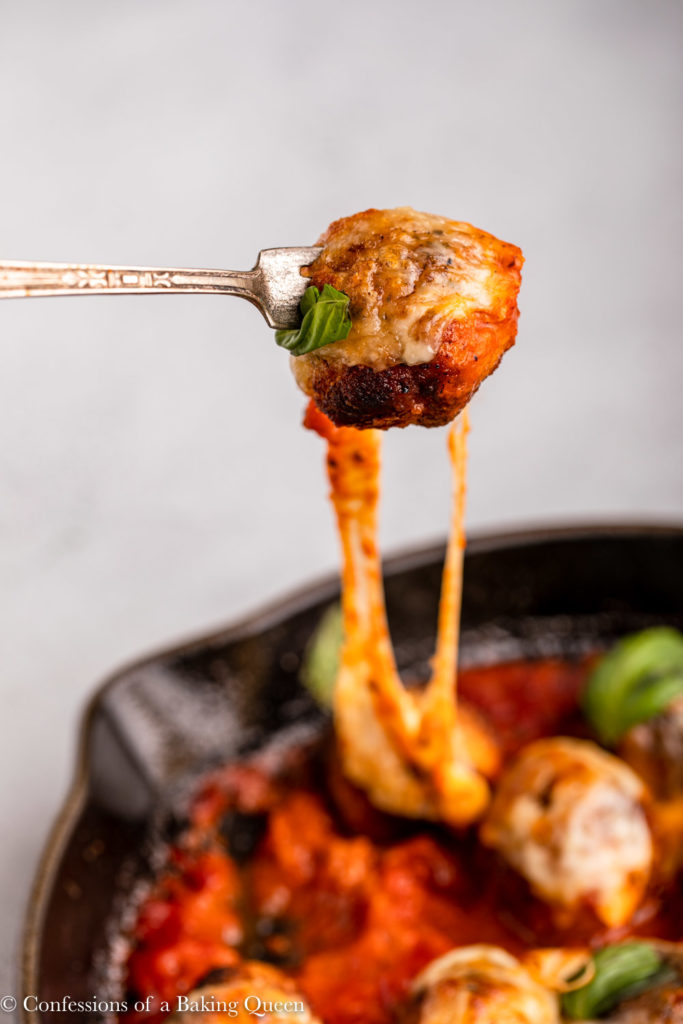 fork holding a chicken parmesan meatball pulling cheese from the skillet