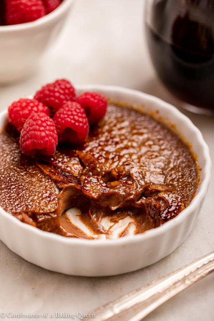 half eaten chocolate creme brulee with raspberries next to a spoon