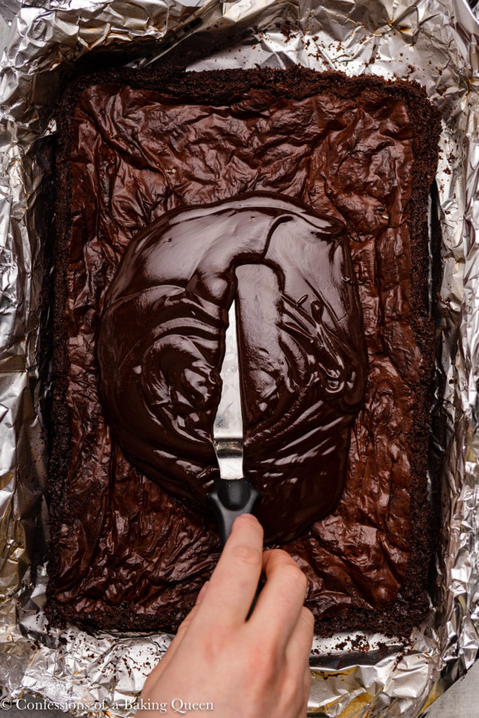 hand holding an angled spatula spreading chocolate frosting on top of brownies