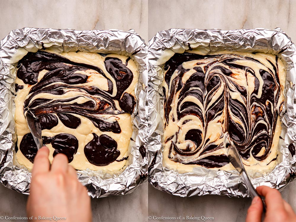 hand swirling brownie batter into cheesecake