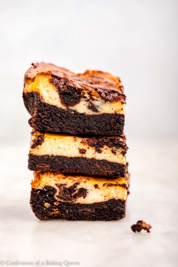 stack of three cheesecake brownies on a white marble surface