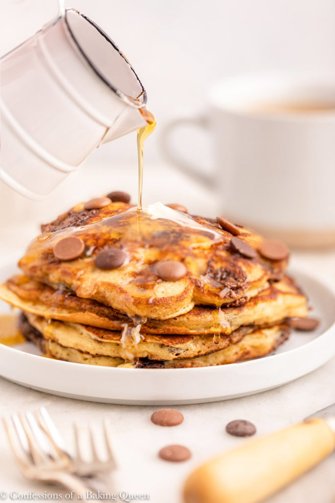 syrup poured on top of a stack of chocolate chip pancakes
