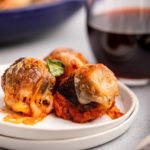 three chicken parm meatballs on a white plate (