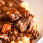 close up of guinness beef stew in a white bowl
