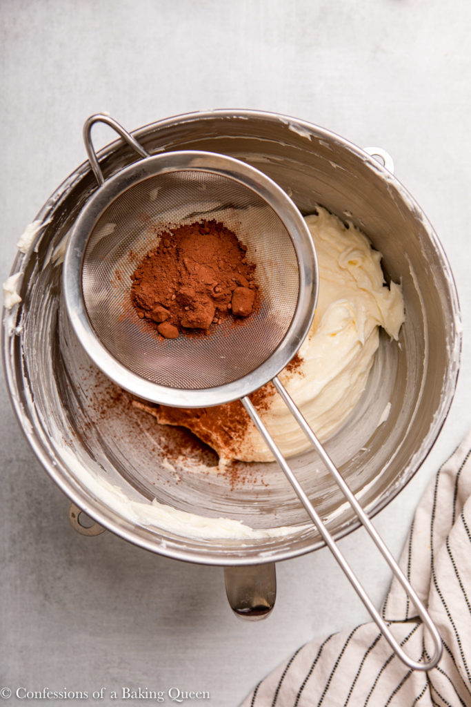 cocoa powder sifted into cream cheese mixture in a metal bowl