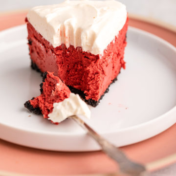 fork with a bit of red velvet cheesecake next to the slice on a plate