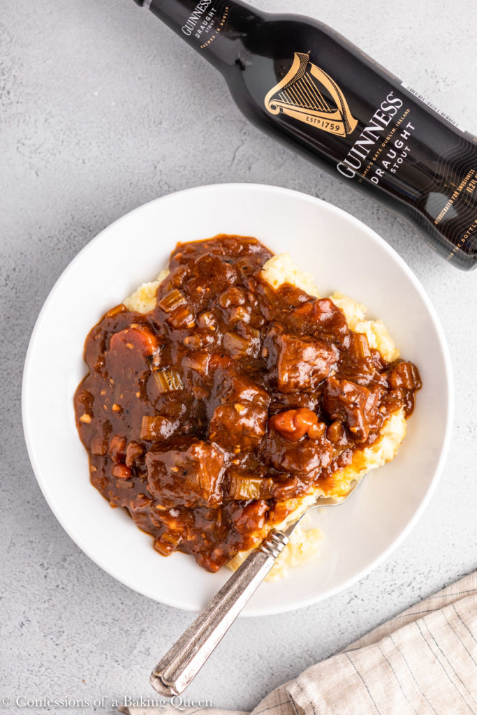 overhead shot of irish stew in a white bowl next to a bottle of guinness