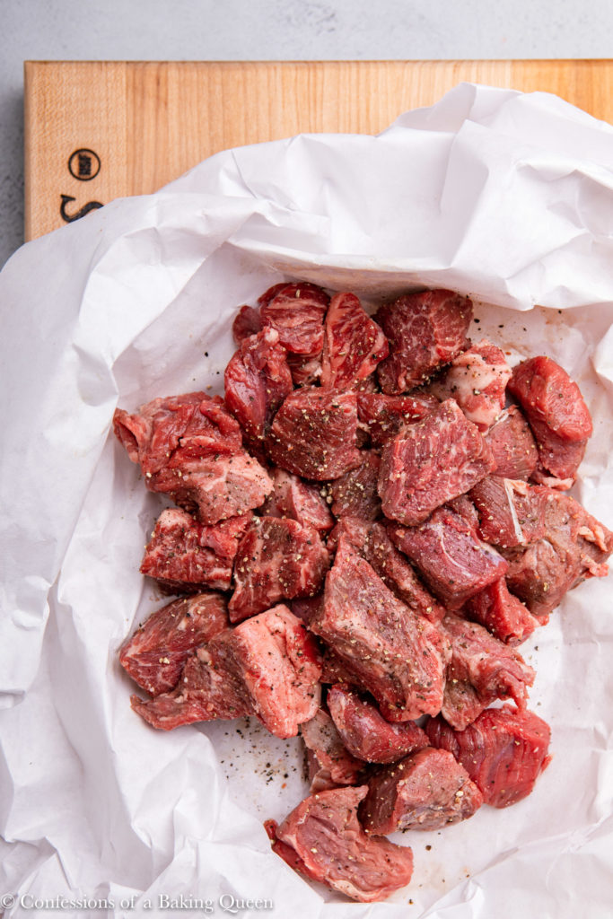 raw stew meat on white paper on a wood board