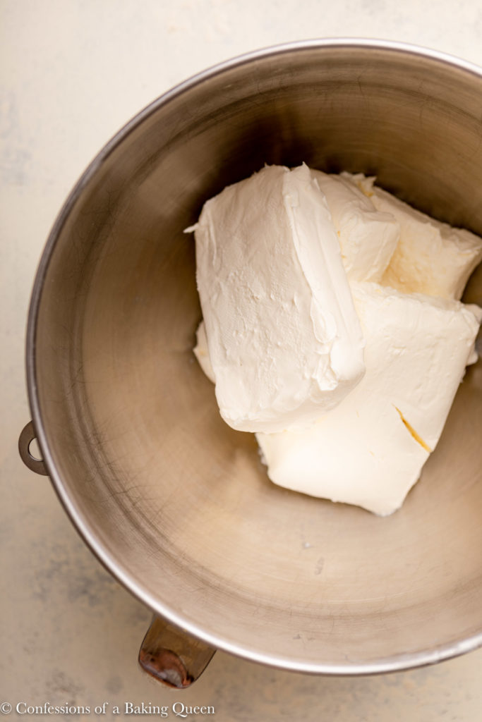 blocks of cream cheese in a metal mixing bowl