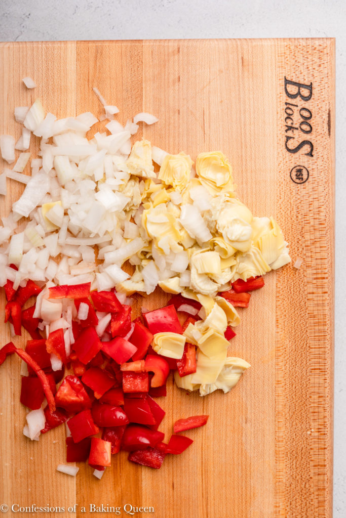 A wooden cutting board with chopped bell peppers, onions, and artichoke hearts