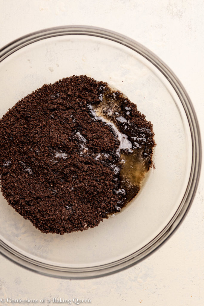 crushed oreos and melted butter in a glass bowl