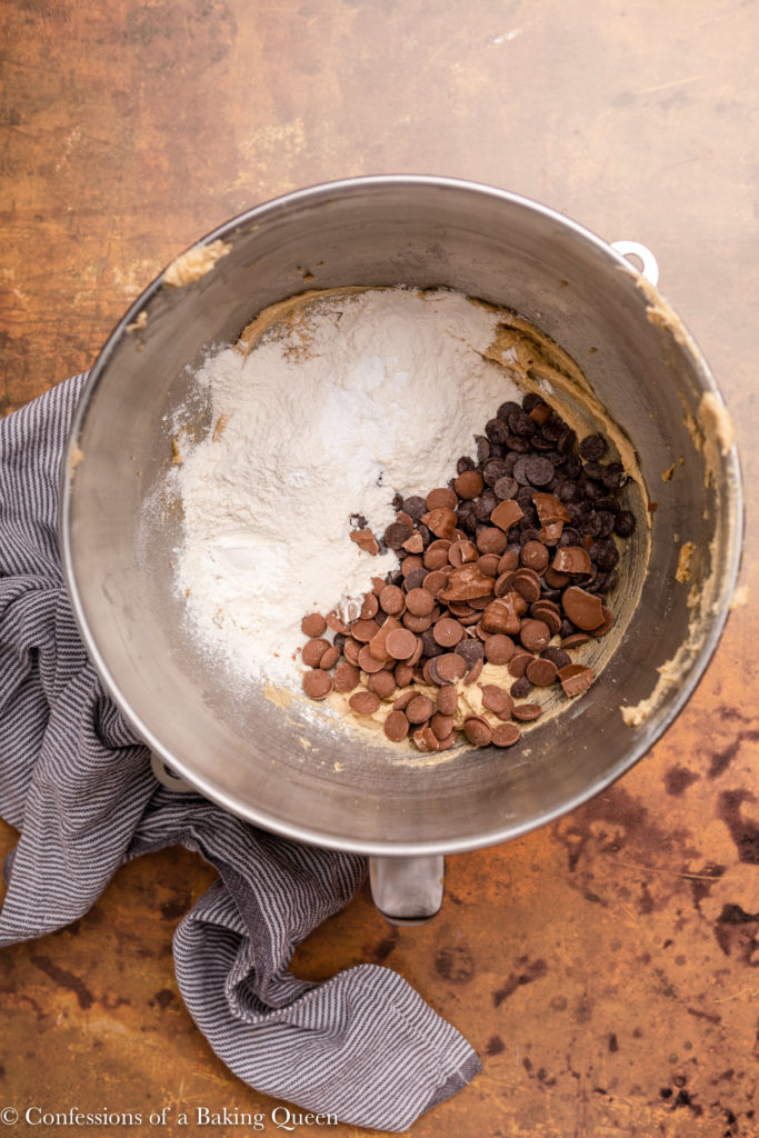flour and chocolate added to wet ingredients in a metal bowl for cookie dough