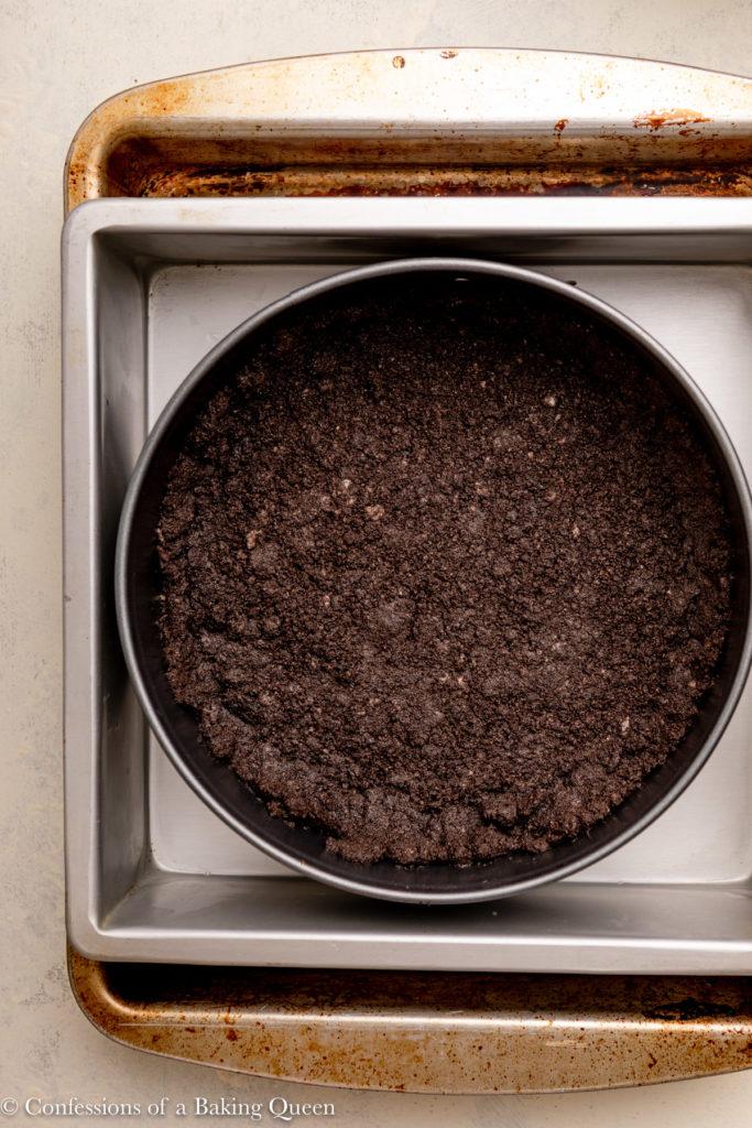 oreo crust in a springform pan in a roasting pan