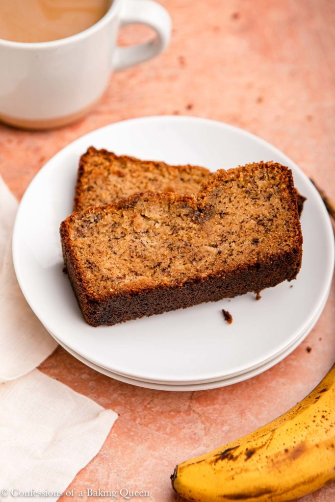 slice of almond flour banana bread on a white plate next to a cup of coffee