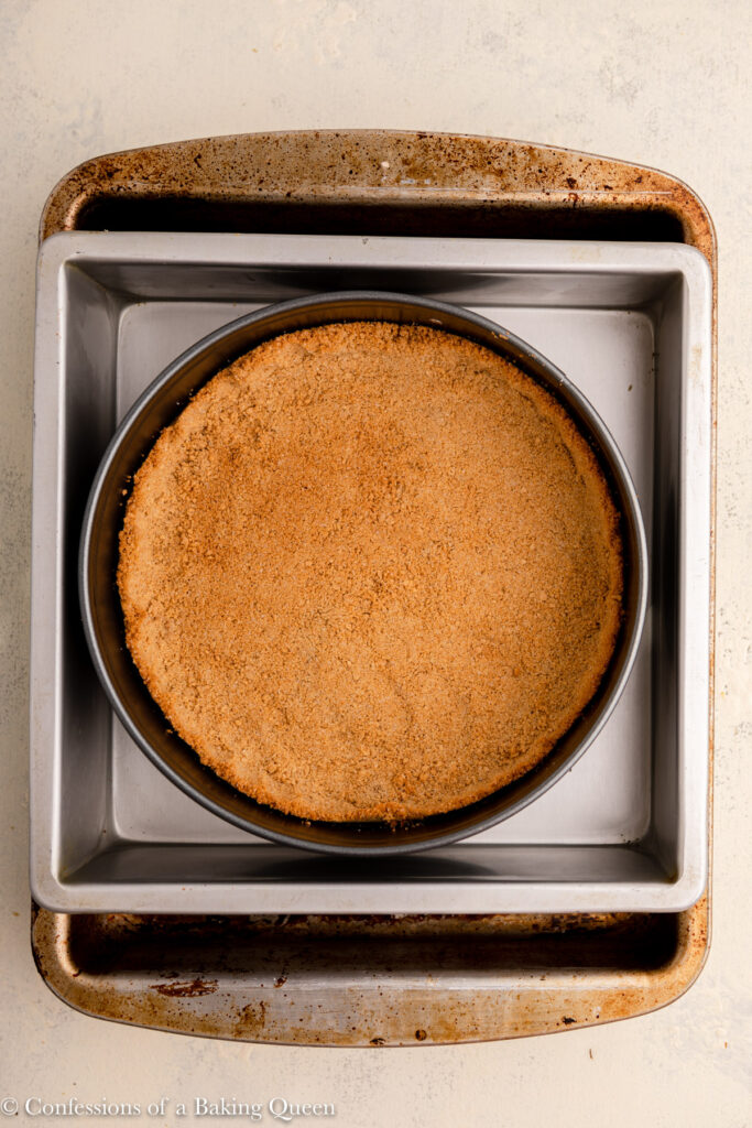 graham cracker crust in a springform pan inside a roasting pan