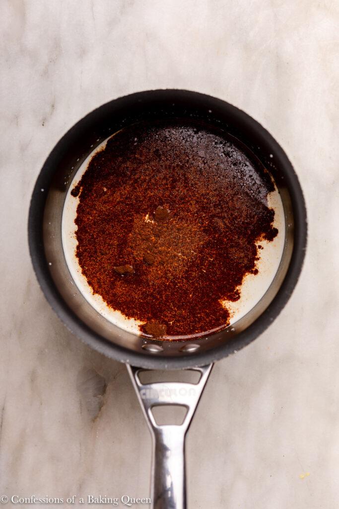 instant espresso powder added to milk in a small pot