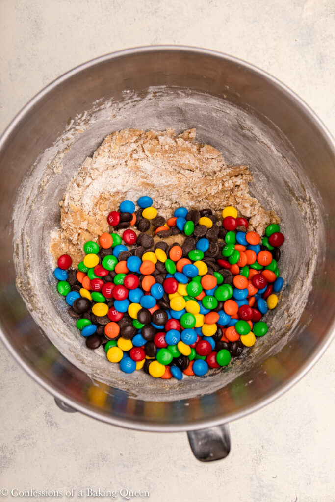 m&ms added to cookie dough in a metal bowl (