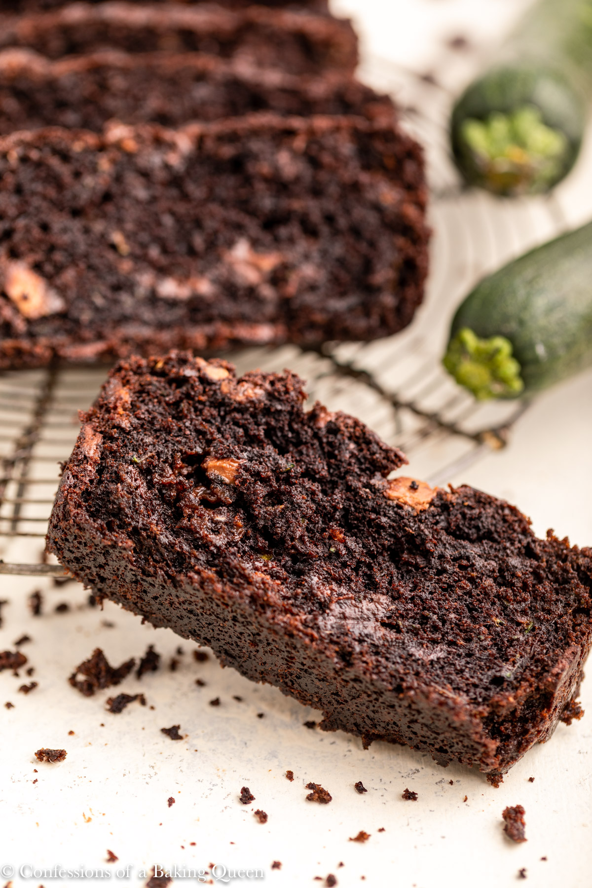 slice of double chocolate zucchini cake hanging off a wire rack