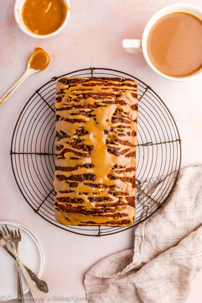 sticky toffee loaf cake on a wire rack next to plates, forks, and a cup of coffee