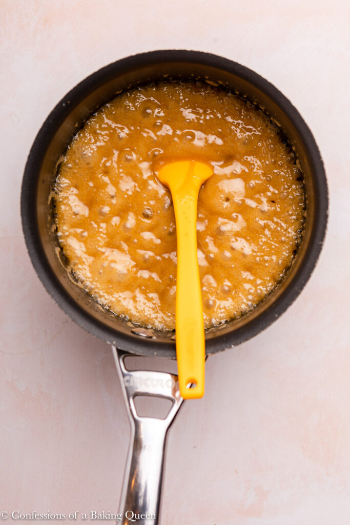 sticky toffee sauce bubbling in a pot with a yellow spatula
