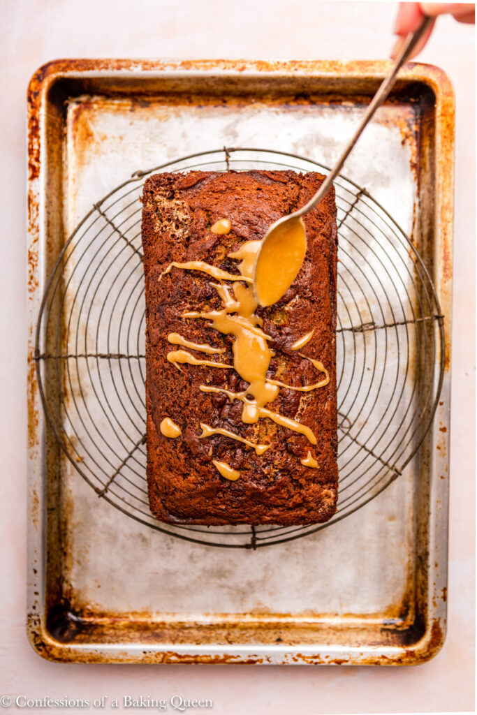 sticky toffee sauce drizzled on top of sticky toffee loaf cake