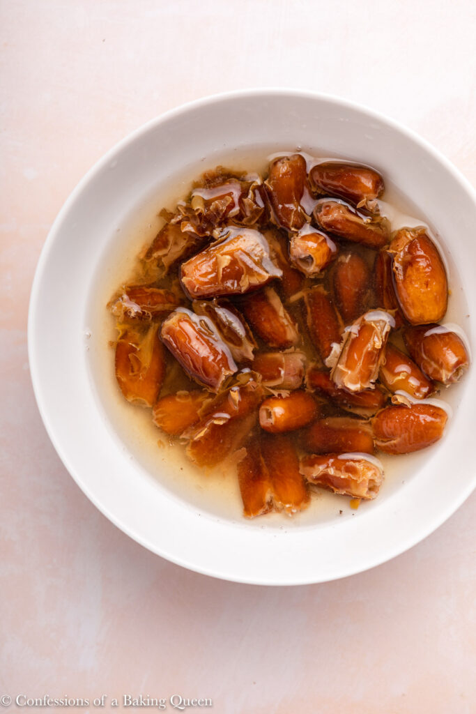 white bowl with dates soaking in hot water